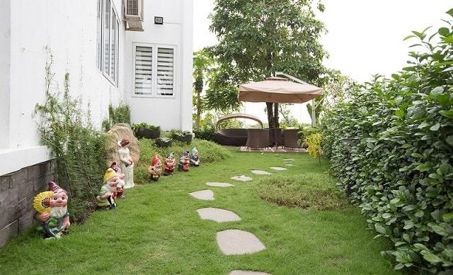 Sân vườn kiểu Âu với thảm cỏ, bồn cây cây cao kết hợp sàn gỗ