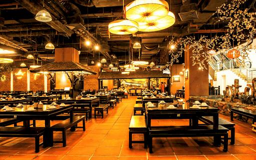 Khung cảnh nhà hàng thiết kế ấm cúng với ánh điện màu vàng cam cùng những bộ bàn ăn bằng gỗ
