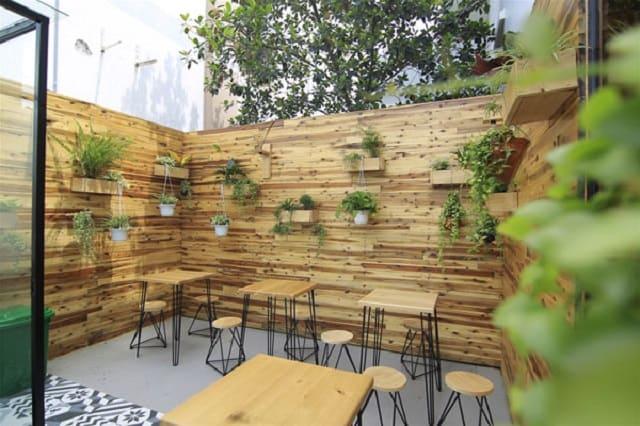 Sử dụng vách ngăn bằng gỗ, không giản mở ngoài trời kết hợp với chậu cảnh nhỏ mang lại vẻ đẹp gần gũi cho quán trà sữa